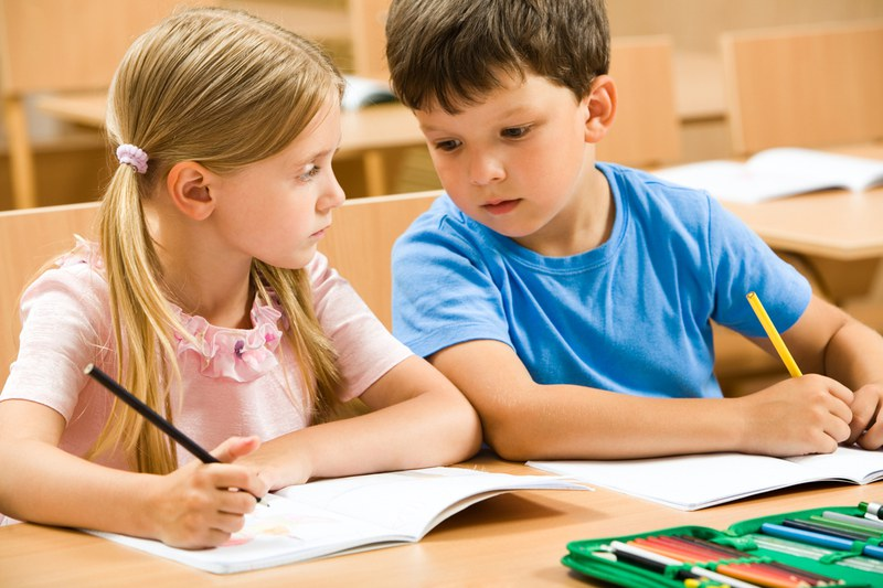 Two children are sitting on a desk and holding pens in their hands