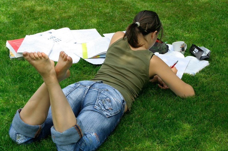 female student learning in the grass