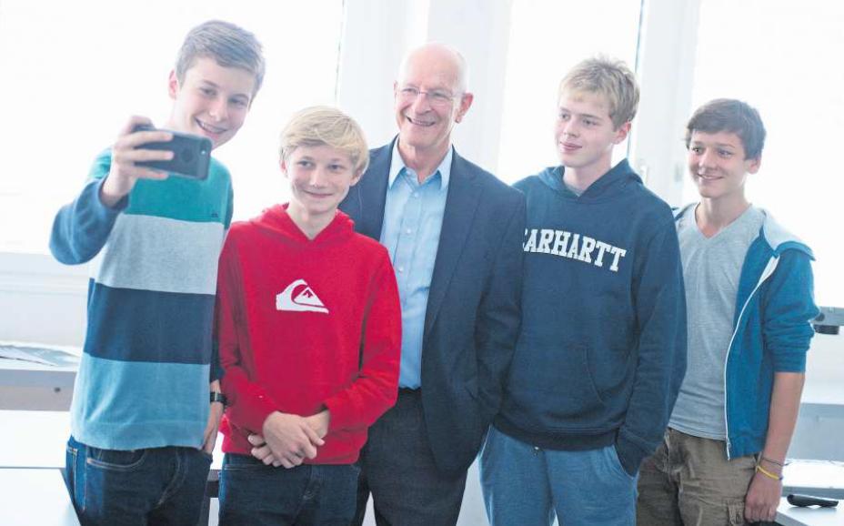 Claude Nicollier (Mitte) lässt sich mit Schülern der Kantonsschule Zug ablichten.