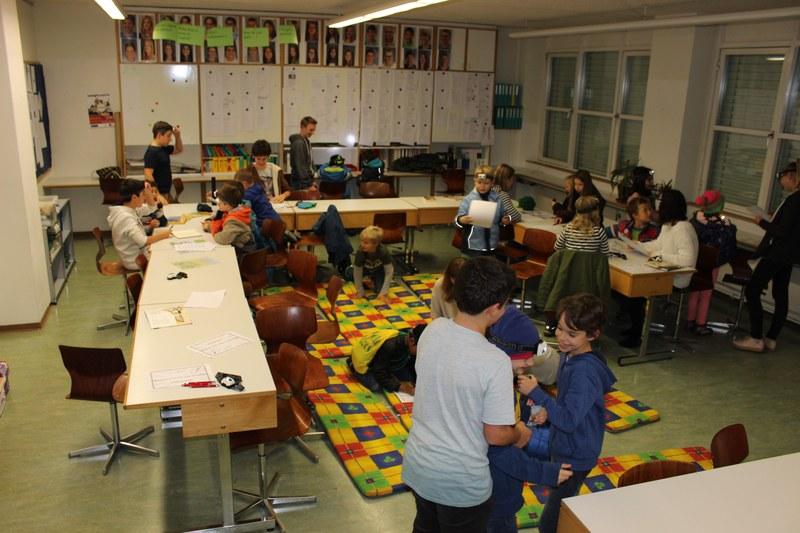 Die Grossen schauen zu den Kleinen: 2. Klässler und Jugendliche der 3. Oberstufe arbeiten mit den Lesespuren.