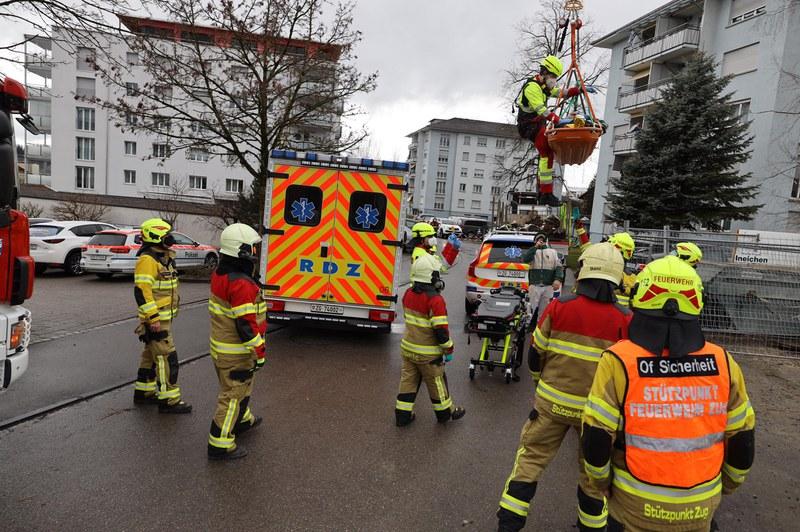 Verletzter Bauarbeiter wird mit dem Baukran zum Rettungswagen herabgelassen.