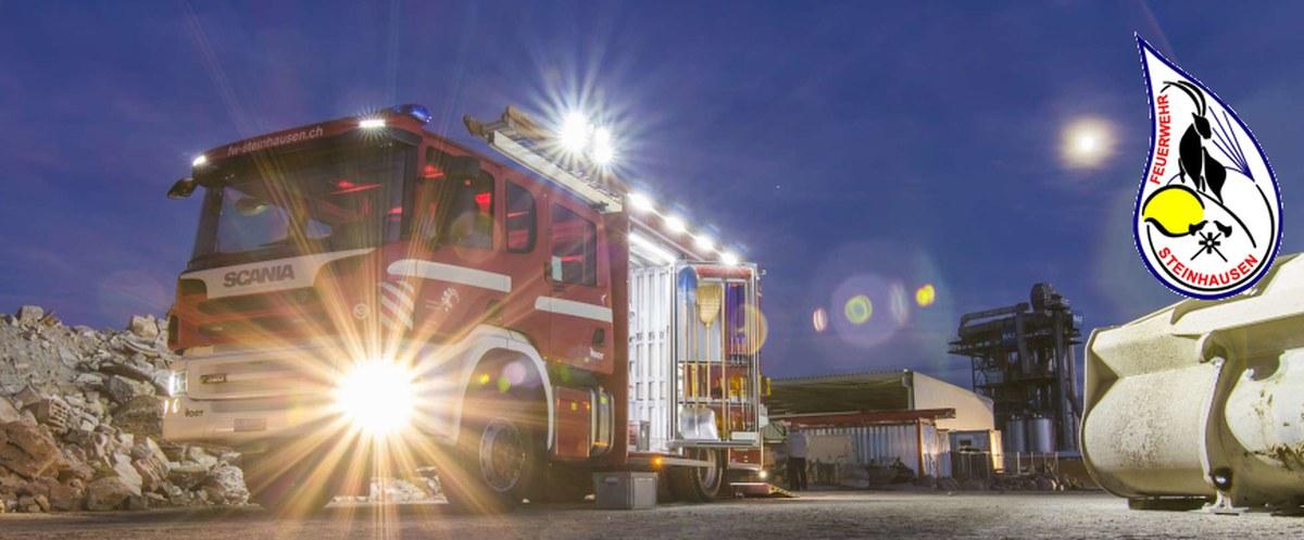 Feuerwehrfahrzeug nachts in Aktion mit Beleuchtung